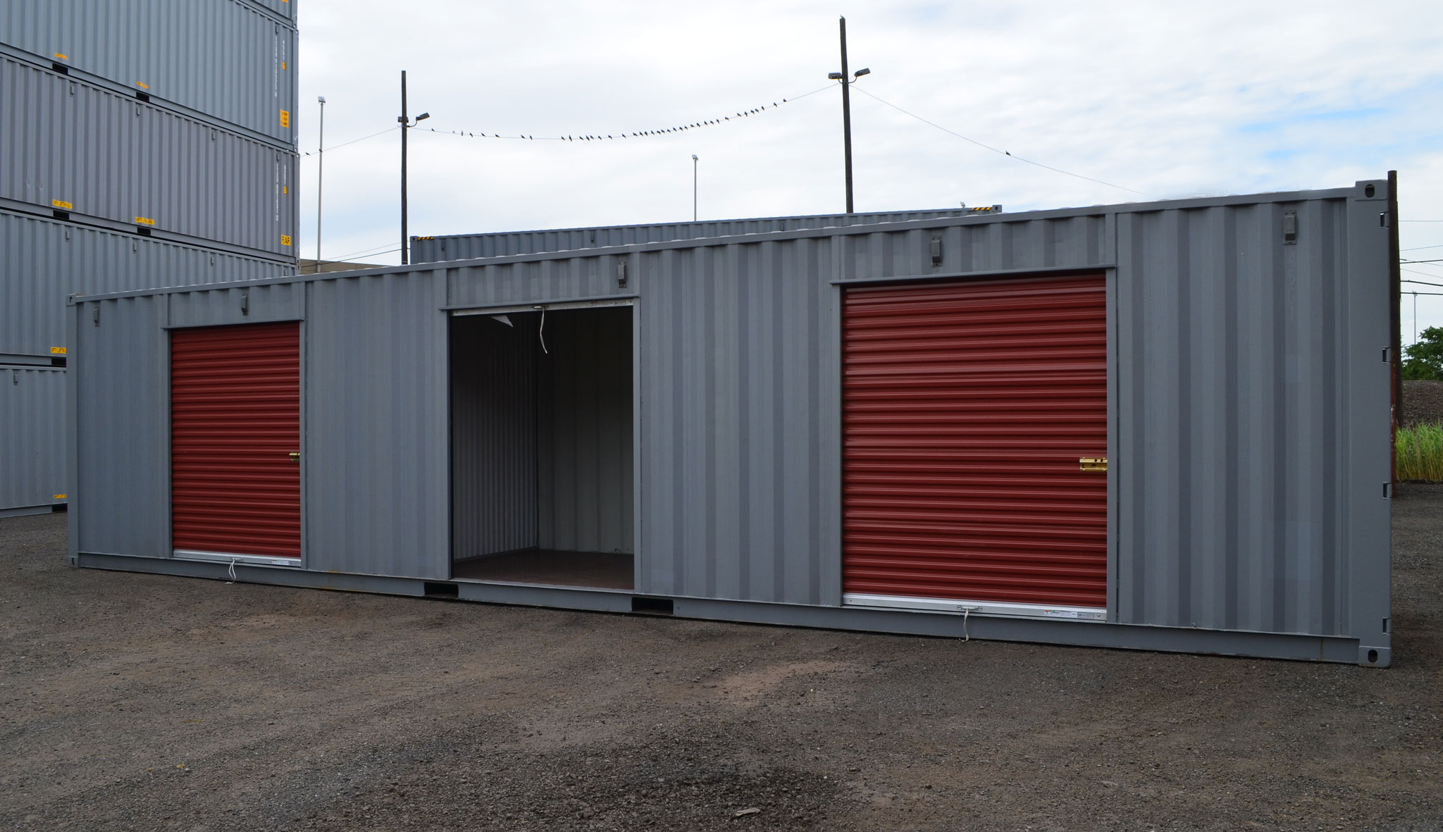 Storage Container with Three Roll Up Doors One Open